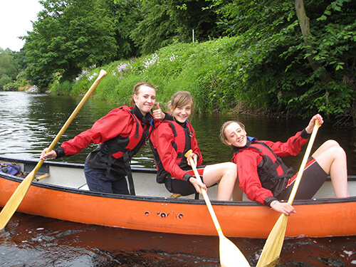 Three girls canoeing