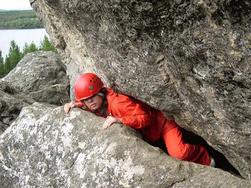 Weaseling - a child climbing between rocks